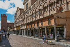 View of old building with people and shops, near the Ferrara Cathedral. Stock Image