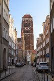Zlotnikow and St. Mary`s Street Church in Gdansk. View of old buildings on the Zlotnikow Street and St. Mary`s Church at the Main Town Old Town in Gdansk, Poland Royalty Free Stock Photo