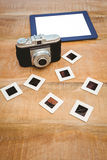 View of an old camera and a blue tablet. On wood desk Royalty Free Stock Photography
