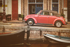 View at an old canal in Amsterdam. With boats and a parked classic car Stock Photography