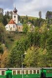 View of the old church Sankt Georgen am Gasenbach and narrow gauge railway wagon Feistritztalbahn. Koglhof, Austria Stock Photos