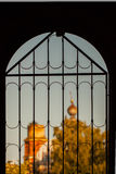 View of old church through window with bars Royalty Free Stock Photos