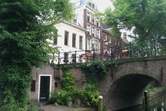 A view of the old city center of Utrecht from the canal. Looking up at an old bridge and old Dutch frontages royalty free stock photos