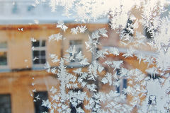 View of the old city house from a frozen winter window. Texture ice patterns on glass. Selective focus.  Royalty Free Stock Photography
