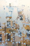 View of the old city house from a frozen winter window. Texture ice patterns on glass. Selective focus.  Stock Photos