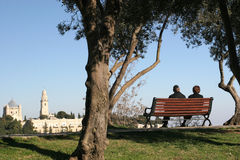 View Of the old city, from local park, Jerusalem. Jewish couple sitting on a jerusalem Park Bench overlooking the Old City stock images