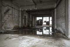 Old empty warehouse interior. Reflections in puddle Stock Image