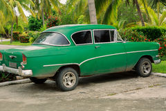 view of old green, customized retro vintage , classic car parked in tropical garden Royalty Free Stock Images