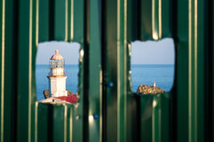View of the old lighthouse. Framed with a holes in the fence Stock Photography