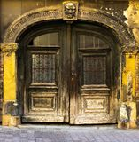 View of an old massive carved wooden door with an sculptured arch and yellow facade, Zagreb in Croatia royalty free stock image