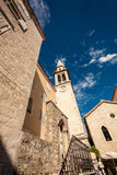 View of old narrow street with high clock tower Royalty Free Stock Photography