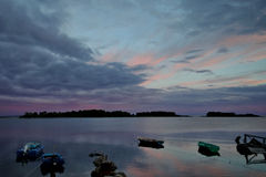 View of the old pier, boats and islands at sunset. Russia Solovetsky Islands, Solovki village Royalty Free Stock Image