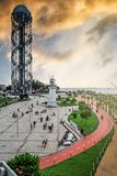 View of old Pitsunda Lighthouse In Miracle Park, Batumi. Top view of old Pitsunda Lighthouse in Miracle Park. People walking along embankment Stock Photo