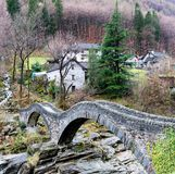 View of the old Roman stone bridge with two arches near the village of Lavertezzo in the Swiss Alps. Of the Ticino Royalty Free Stock Images