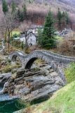 View of the old Roman stone bridge with two arches near the village of Lavertezzo in the Swiss Alps. Of the Ticino Stock Photos