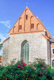 View of old stone Catholic parish building. With orange brick roof, arcade window and blooming tea rose bush on a sunny summer day, Poland, Krakow Royalty Free Stock Photography