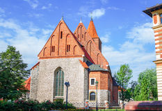 View of old stone Catholic parish building. With orange brick roof, arcade window and blooming tea rose bush on a sunny summer day, Poland, Krakow Royalty Free Stock Photo