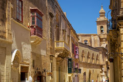 A view of old street with Carmelite Church Bell Tower on the bac. MDINA, MALTA - JULY 29, 2015: A view of old Mdina street with a traditional Maltese style Stock Images