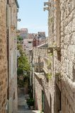 View at old town in Hvar from little alley surrounded by masonry buildings. stock image