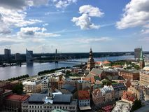 View of the Old Town in Riga, capital of Latvia. Viewed from St Peters Church looking over the Daugava River on a sunny blue sky day with clouds Royalty Free Stock Photo