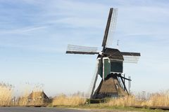 View on an old tradional windmill in the Netherlands, part of historic Dutch culture. The wind makes the blades rotate to provide energy to drain the land so royalty free stock photo