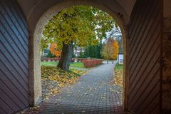 View from open arched wooden door to autumn landscape. Slokenbeka manor. stock photos