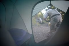 View through the open flap of a tent. Of two men working in a campsite in early morning mist or smoke from a camp fire Stock Photography