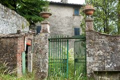 Open green gate at an abandoned Italian Villa. View of an open green gate at an abandoned Italian Villa with overgrown yard, in the tiny rural village of Stock Images