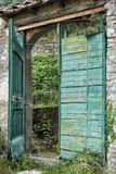 Open green gate at an abandoned Italian Villa. View of an open green gate at an abandoned Italian Villa with overgrown yard, in the tiny rural village of Stock Photo