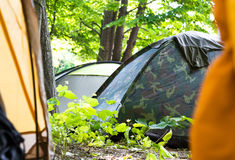 View through an open tent door of a campsite. Under leafy green trees with other closed tents visible pitched in the shade in a concept of adventure and a stock image