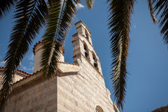 View on orthodox church through palm tree leaves Stock Image