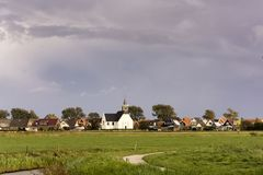 View on Oudeschild, a small historic town on the Wadden Island Texel, the Netherlands. The surroundings of the village with the white small church are rural royalty free stock photos