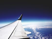 Airplane wing over cloudy earth surface with dark blue horizon royalty free stock photo