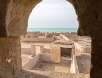 A view out of minaret`s window to the sea. Ruined old town Al Jumail, Qatar. Middle East. Persian Gulf. royalty free stock images