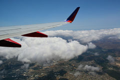 View out plane window of wing and clouds Stock Images