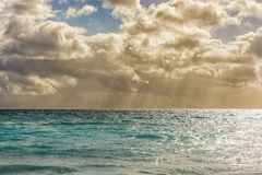 Gentle sea with small waves and a beautiful cloudy sky with sunbeams royalty free stock image