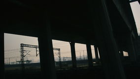 View out of the window of a moving high speed train under the bridge. Heavy fog, dark smog creates oppressive atmosphere. View out of the window of a moving high stock video