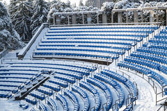 View of outdoor amphitheater rows of  blue plastic seats covered in snow at winter time on sunny day Stock Image