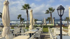 Outdoor cafe near the sea. View on the outdoor cafe with tables, chairs and closing parasols. Green palms surrounds a place of relaxation. People walks at stock video footage