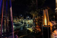 View of outdoor propane heater turned on against backyard background decorated with various lights at winter time stock photography