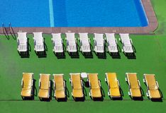 View of an outdoor swimming pool from above with sun loungers an sunlit ripples on the water. A view of an outdoor swimming pool from above with sun loungers an stock image