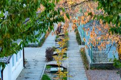 Bird cages in the outdoor zoo with benches. View of outdoor zoo section with bird cages in autumn stock image
