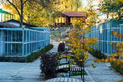 Bird cages in the outdoor zoo with benches. View of outdoor zoo section with bird cages in autumn stock photo