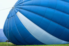 View from outside of a blue-white hot air balloon whan is inflated for flight next to car Royalty Free Stock Photography