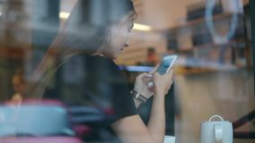 View from the outside of a concentrated young lady with long hair messaging using her mobile phone in the coffee shop stock video footage