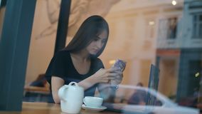 View from the outside of a concentrated young lady with long hair and natural makeup using her mobile phone in the stock video footage