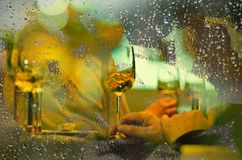 View from outside rainy day a restaurant window. At a table with wine glasses stock photos