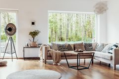 View outside to the green woods through large glass windows in a natural living room interior with beige sofa and dark hardwood fl. Oor concept stock photos