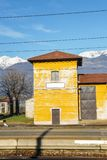 View from outside window of train at small train station and majestic Italian Alps. In the background Stock Photos