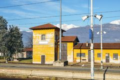 View from outside window of train at small train station and majestic Italian Alps. In the background Royalty Free Stock Images